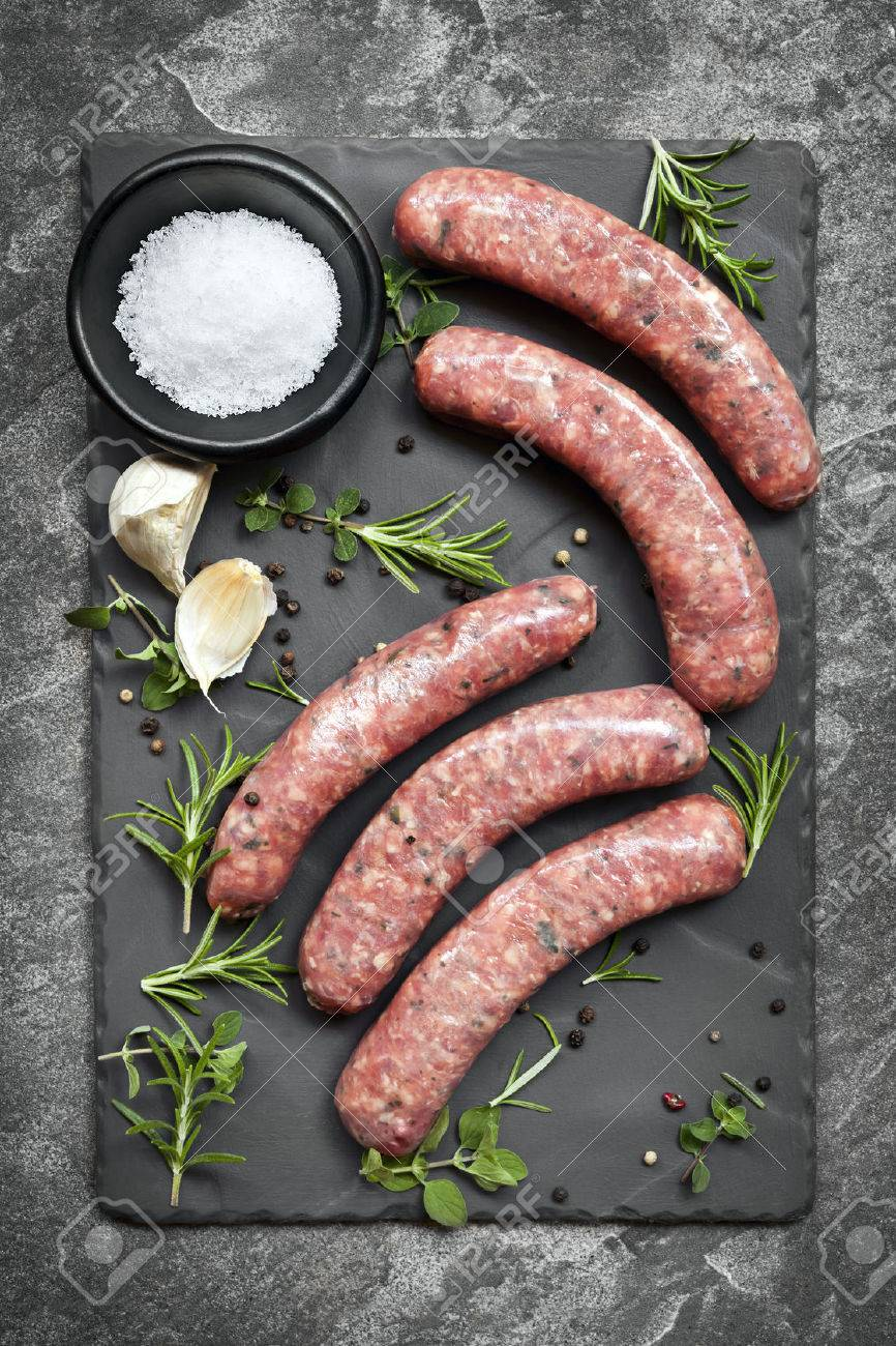 Raw sausages on slate, with herbs and spices. Overhead view. - 51849280