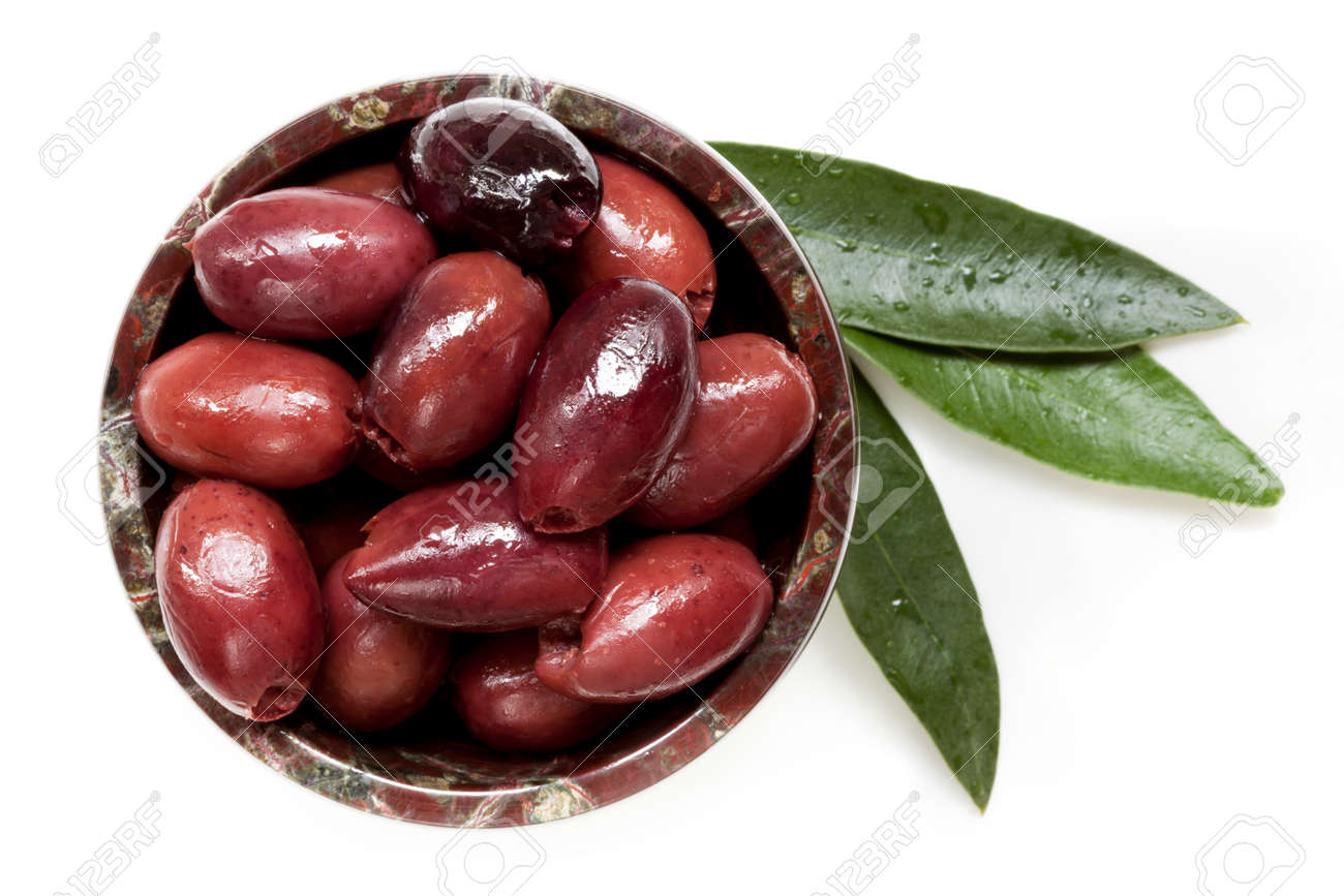 Pitted black kalamata olives in small bowl with leaves, isolated. Top view. - 58917797