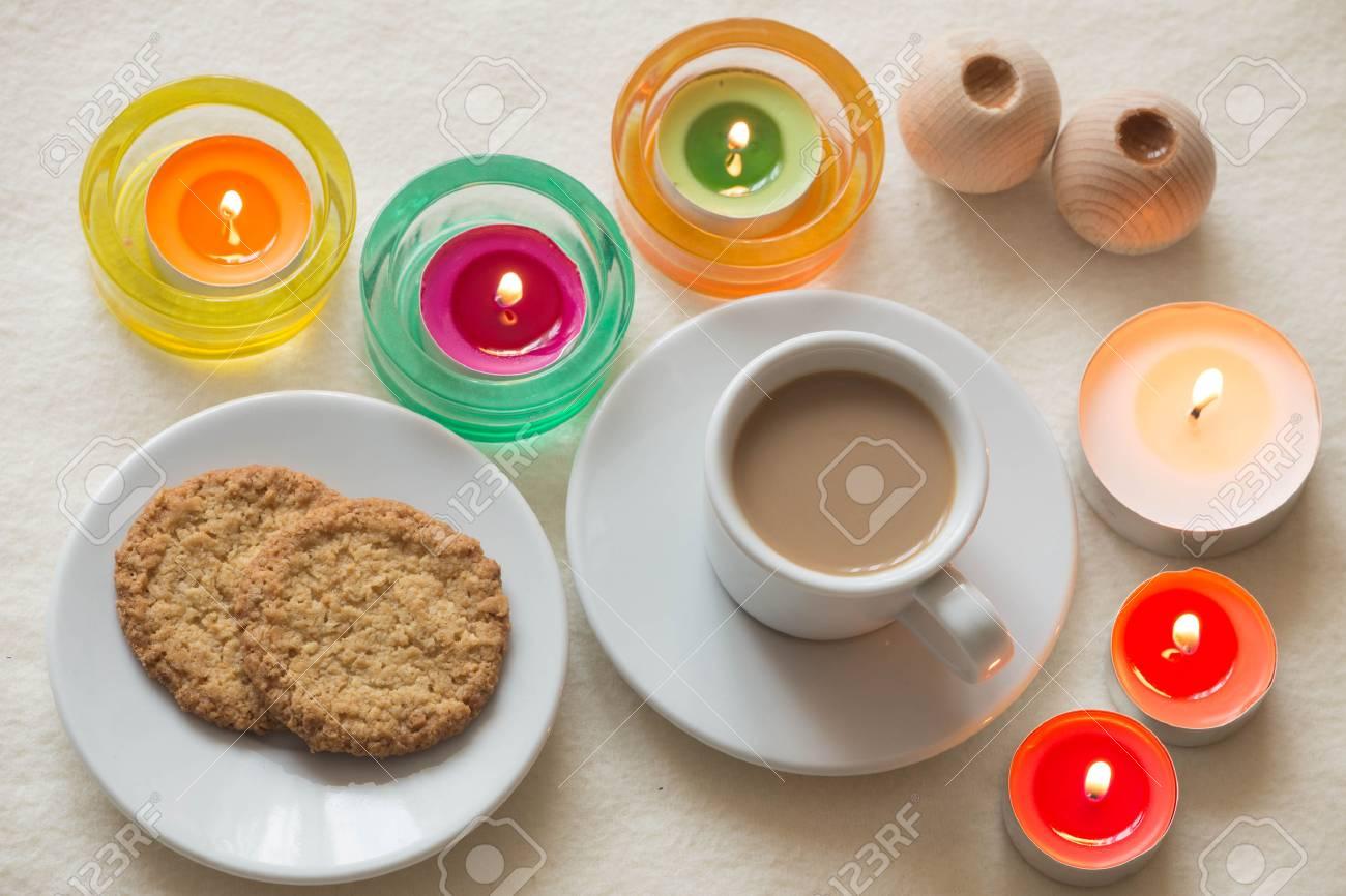 coupe de café fait maison et des biscuits entourés de bougies banque