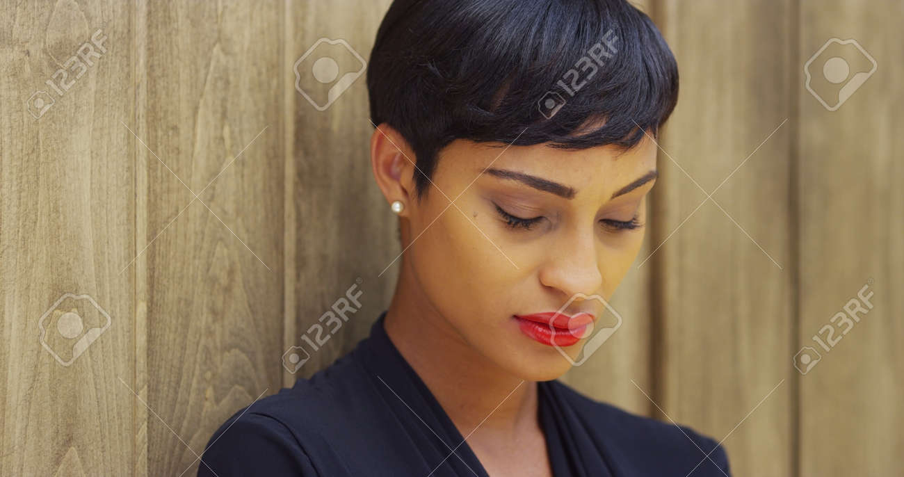 Black dress lipstick - Close Up Of African Woman In Black Dress And Red Lipstick Leaning Against Wall Stock Photo