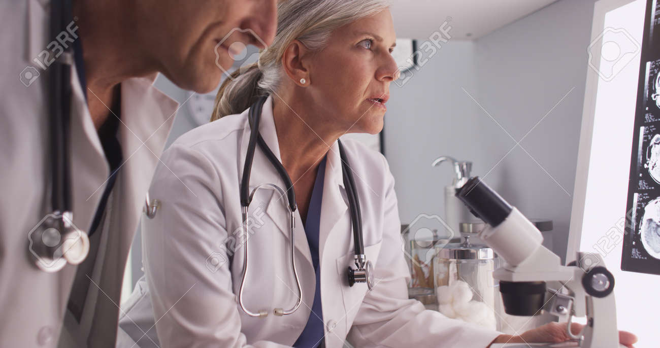 two mature white neurologists studying x-rays stock photo, picture