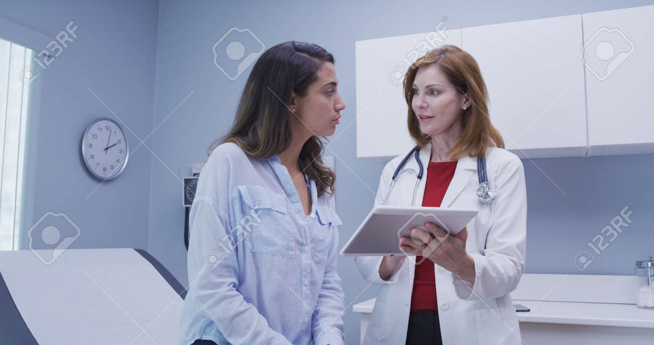 Closeup of doctor using high tech tablet to review health history with patient - 110930285