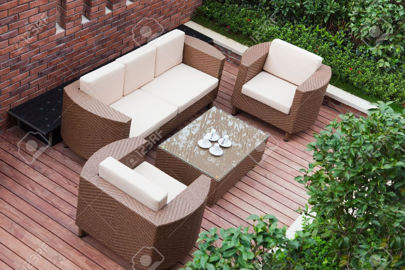 Home exterior patio with wooden decking and rattan sofa view from the top. Stock Photo - 9228560