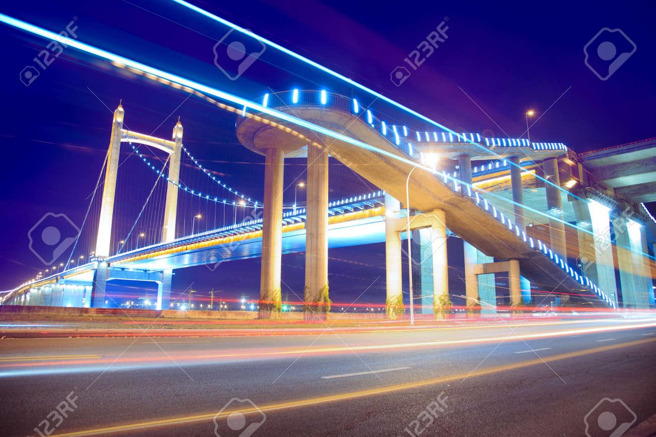 los senderos de luz en el fondo del moderno puente colgante al crepsculo en china