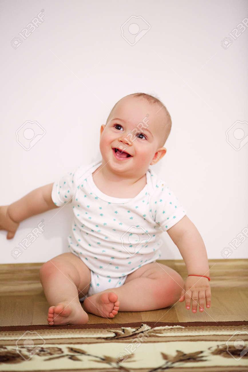 Happy baby boy (1 year old) sitting on floor at children's room. Archivio Fotografico - 96112118