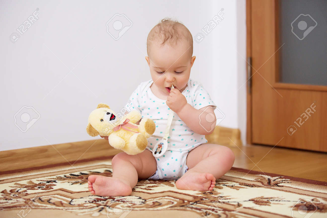 Adorable baby boy playing with plush toy in badroom in sunny day. Archivio Fotografico - 96119437