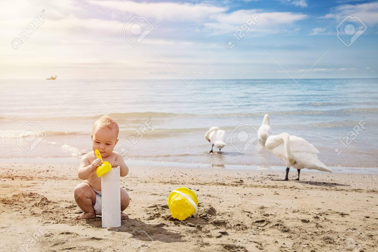 Happy baby boy playng in the sand with yellow scoop in summer day at the beach.Outdoor, close up. Travel and adventure concept. Archivio Fotografico - 96373584