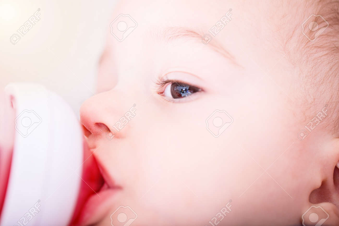 Happy baby boy drinks juice from bottle sitting on chair. Close up portrait. Archivio Fotografico - 96317316