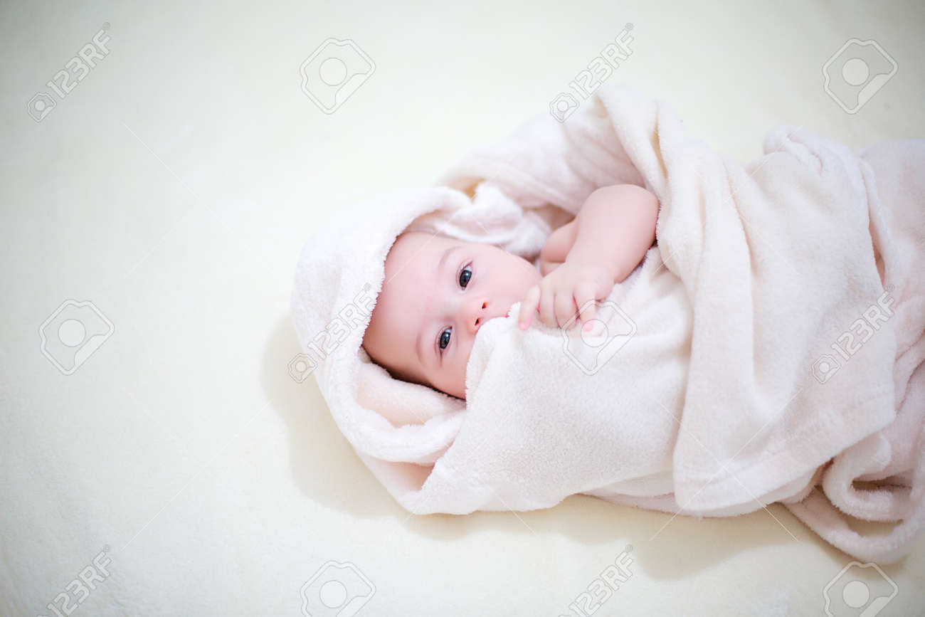 Cute baby wrapped in towels after shower in bed at home. Closeup portrait. Archivio Fotografico - 96317317