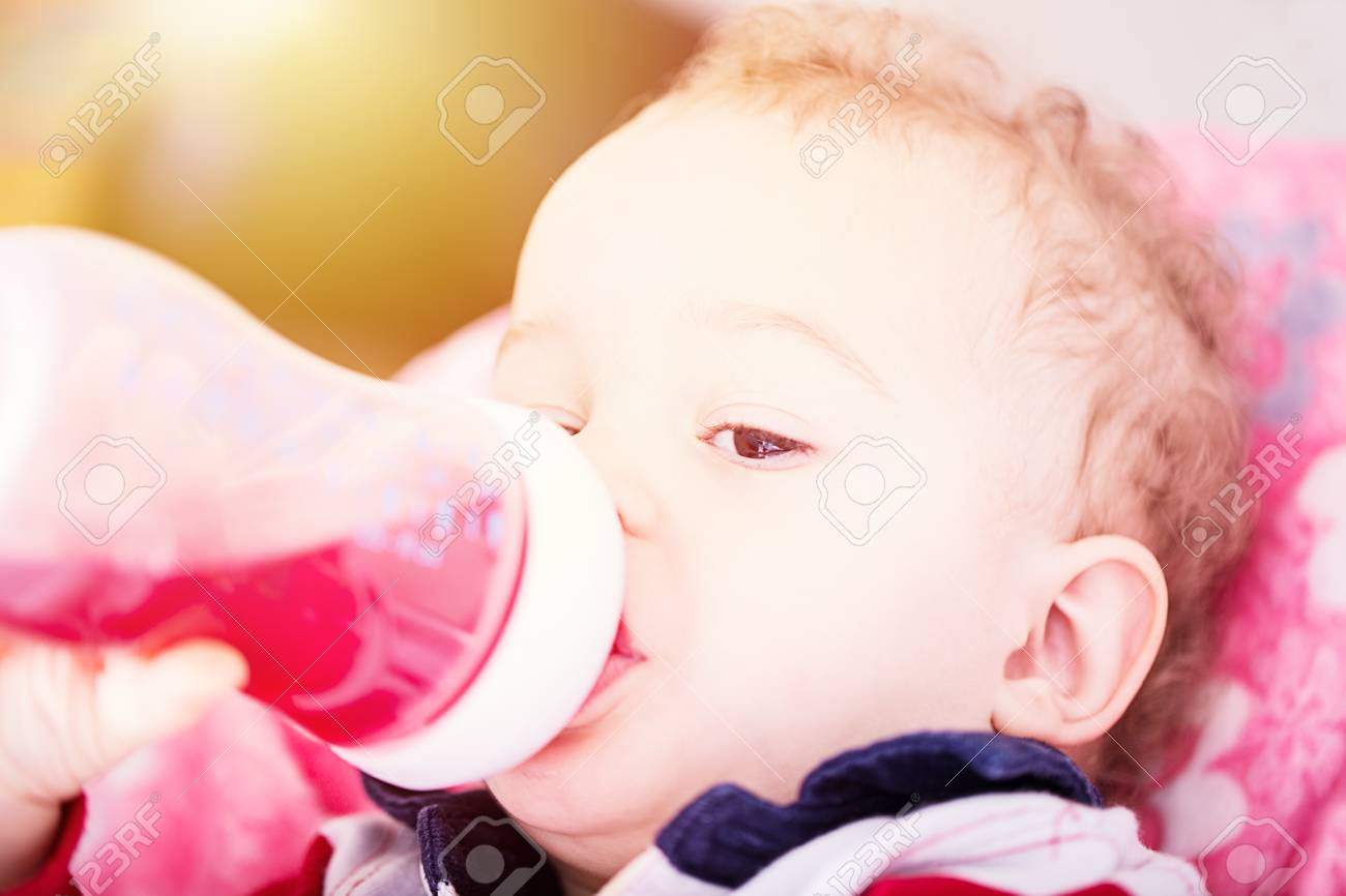 Cute baby drinking water from bottle sitting on chair. Close up portrait. Archivio Fotografico - 96373586