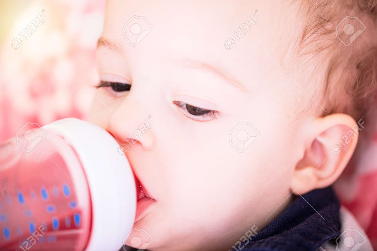 Cute baby boy is drinking water from plastic bottle sitting on chair. Close up portrait. Archivio Fotografico - 96395144