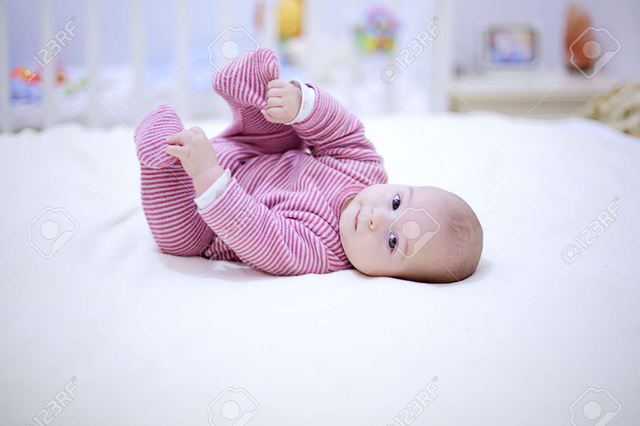 Cute little baby plays with his legs on the bed in bedroom. Archivio Fotografico - 96654501