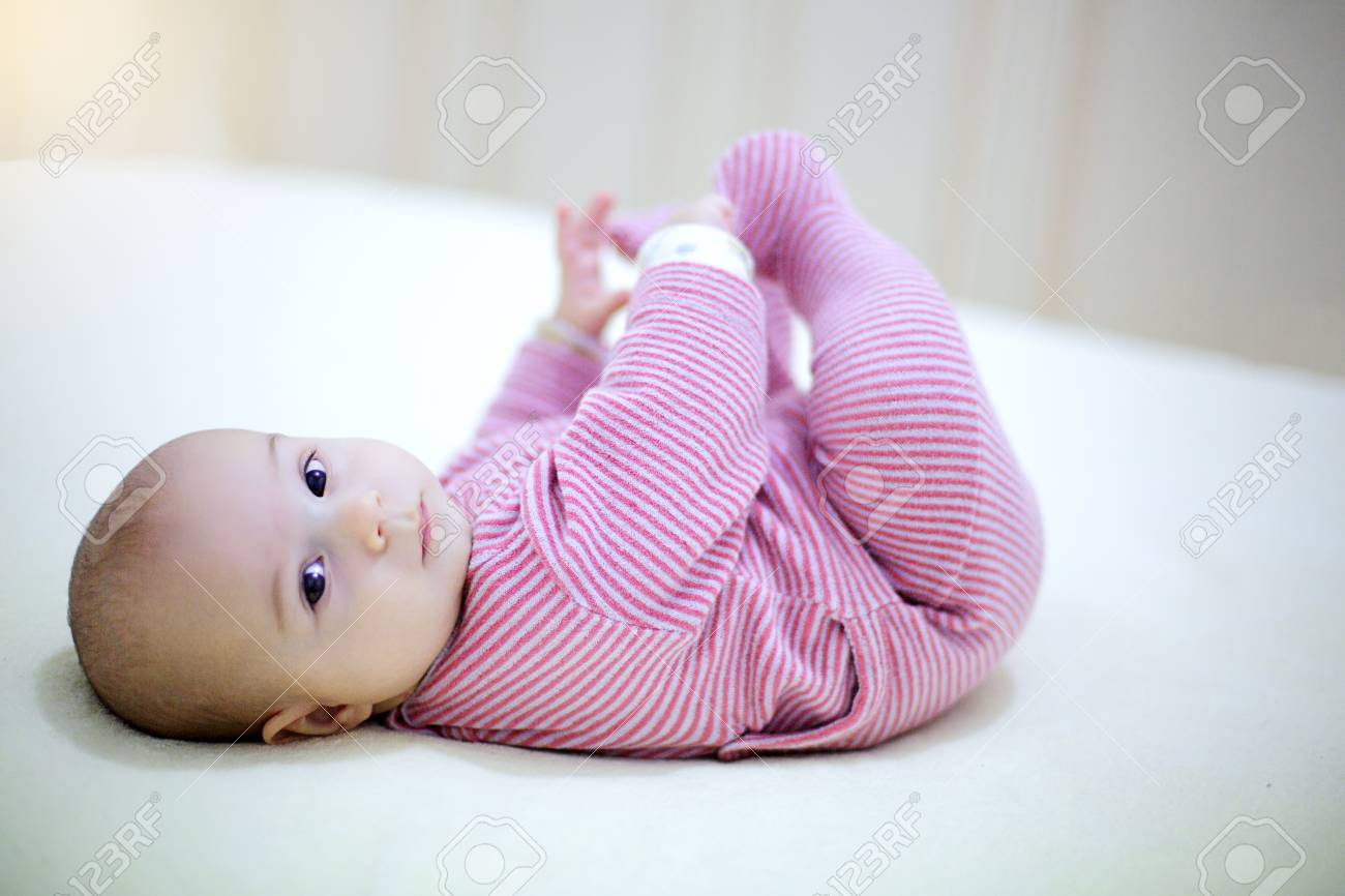 little baby boy playing with his legs on the bed in bedroom. Archivio Fotografico - 96770585