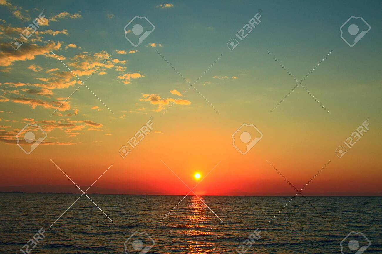 Bright sunset with yellow sun under the sea surface - 120504979