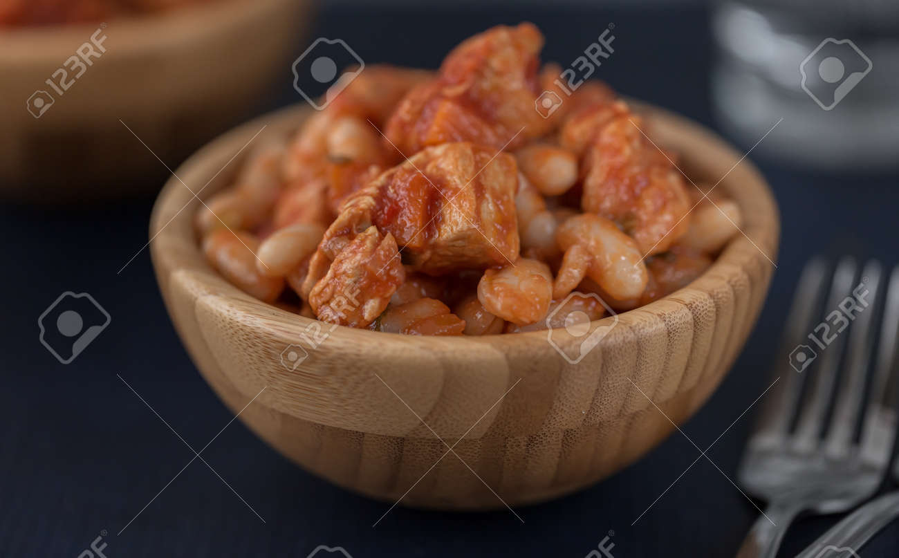 Pork stew with white beans in a wooden bowl. - 166239637