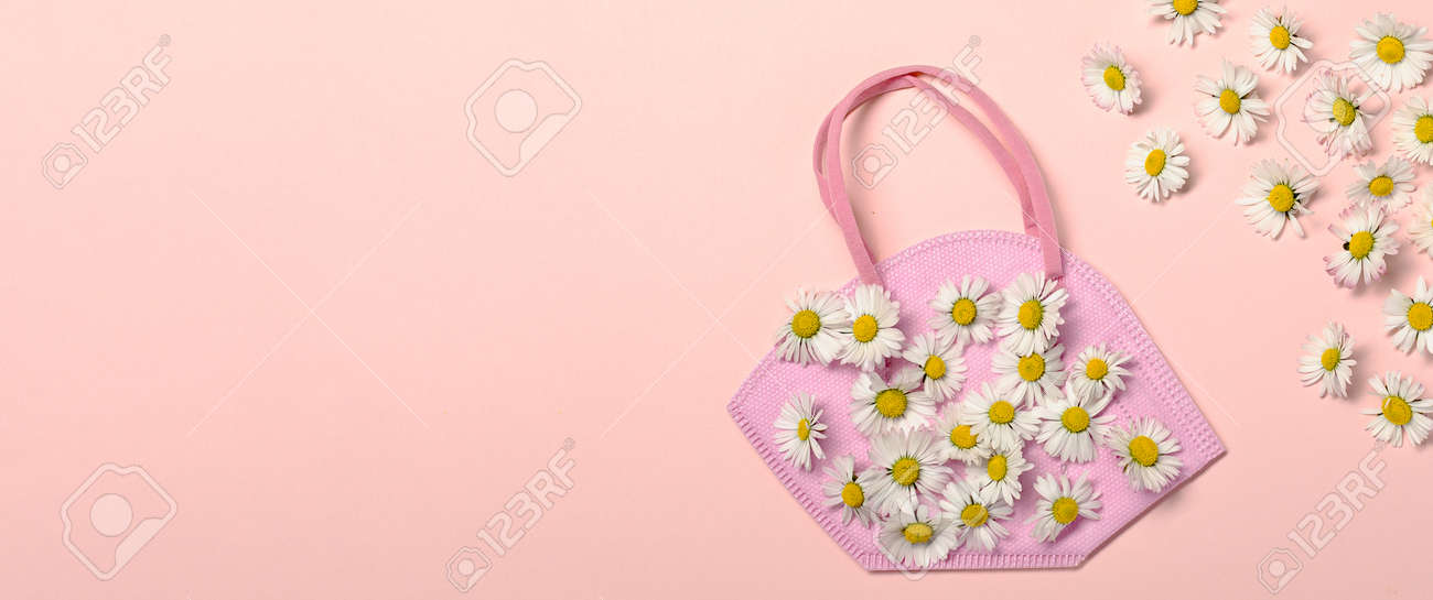 Creative flat lay with daisy flowers and pink fpp2 or KN95 mask - 167779885