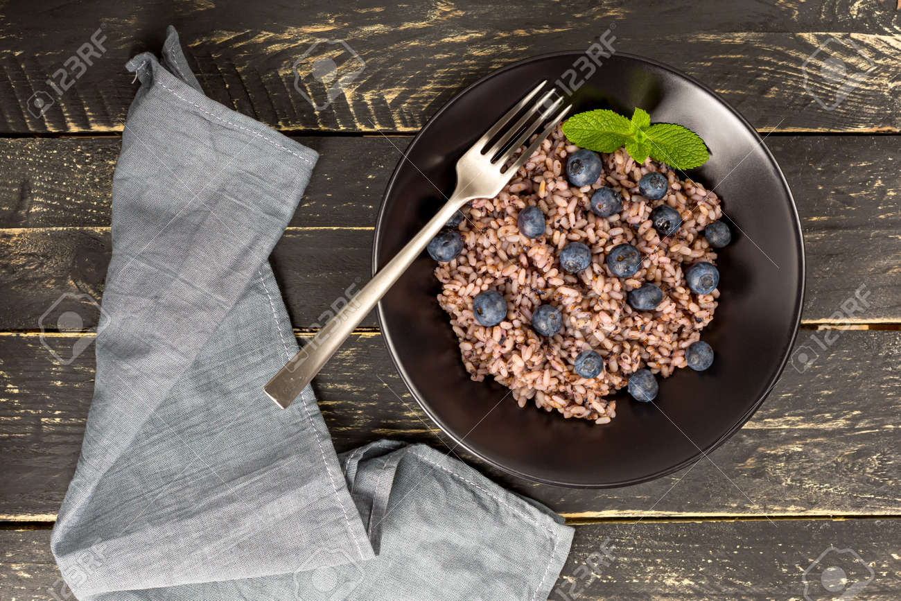 Delicious risotto with blueberries served on dark wooden table, flat lay - 172007885