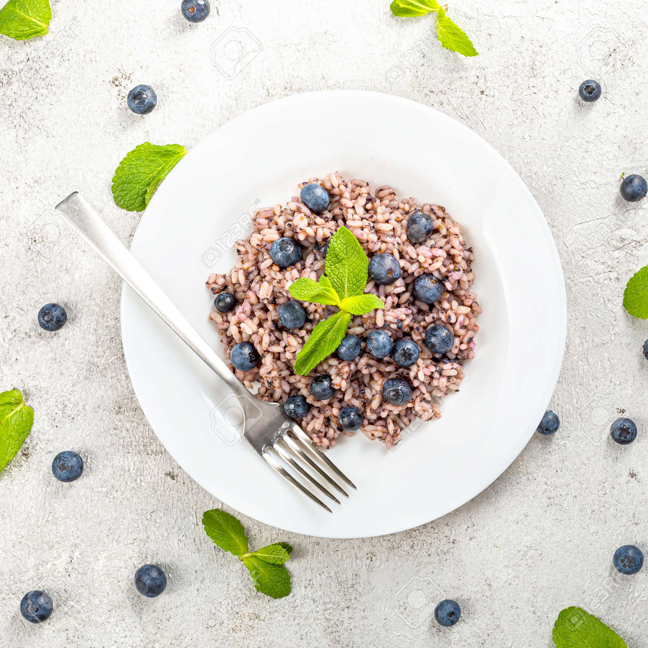 Delicious risotto with blueberries served on lihgt grey concrete table, flat lay - 172007886