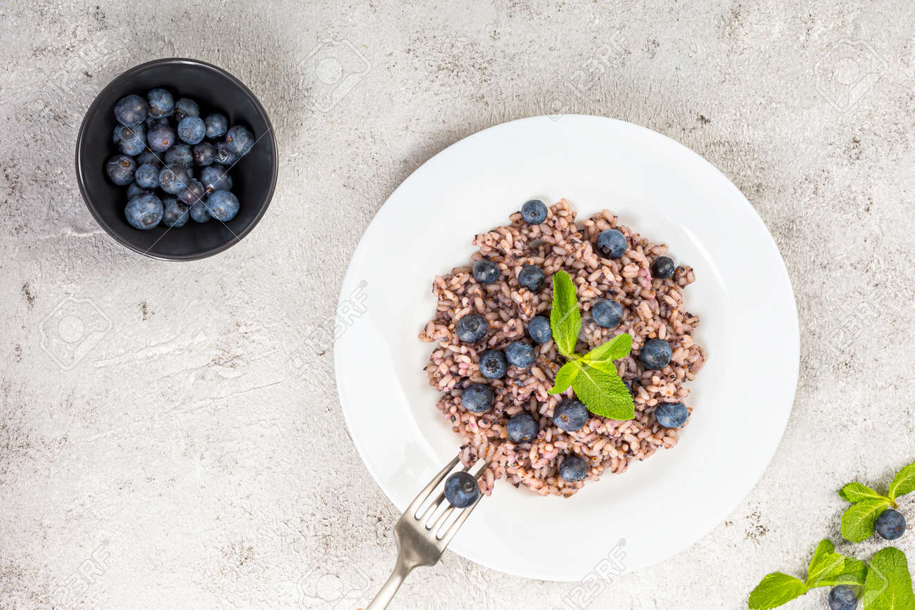 Delicious risotto with blueberries served on lihgt grey concrete table, flat lay - 172007888