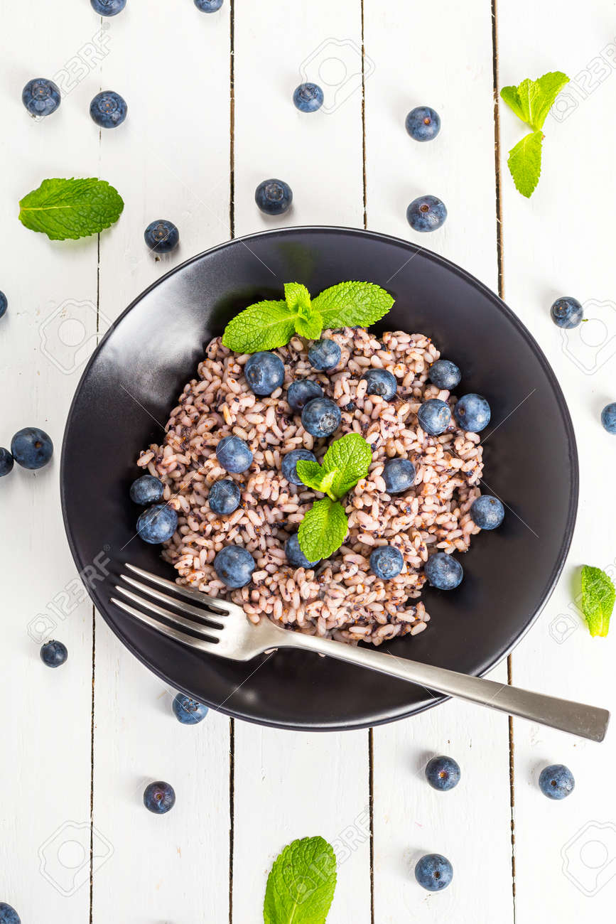 Delicious risotto with blueberries served on white wooden table, flat lay - 172007889