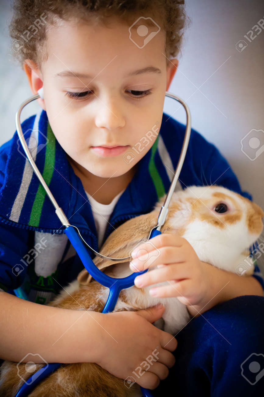 Little child with his bunny on grey. - 173342557
