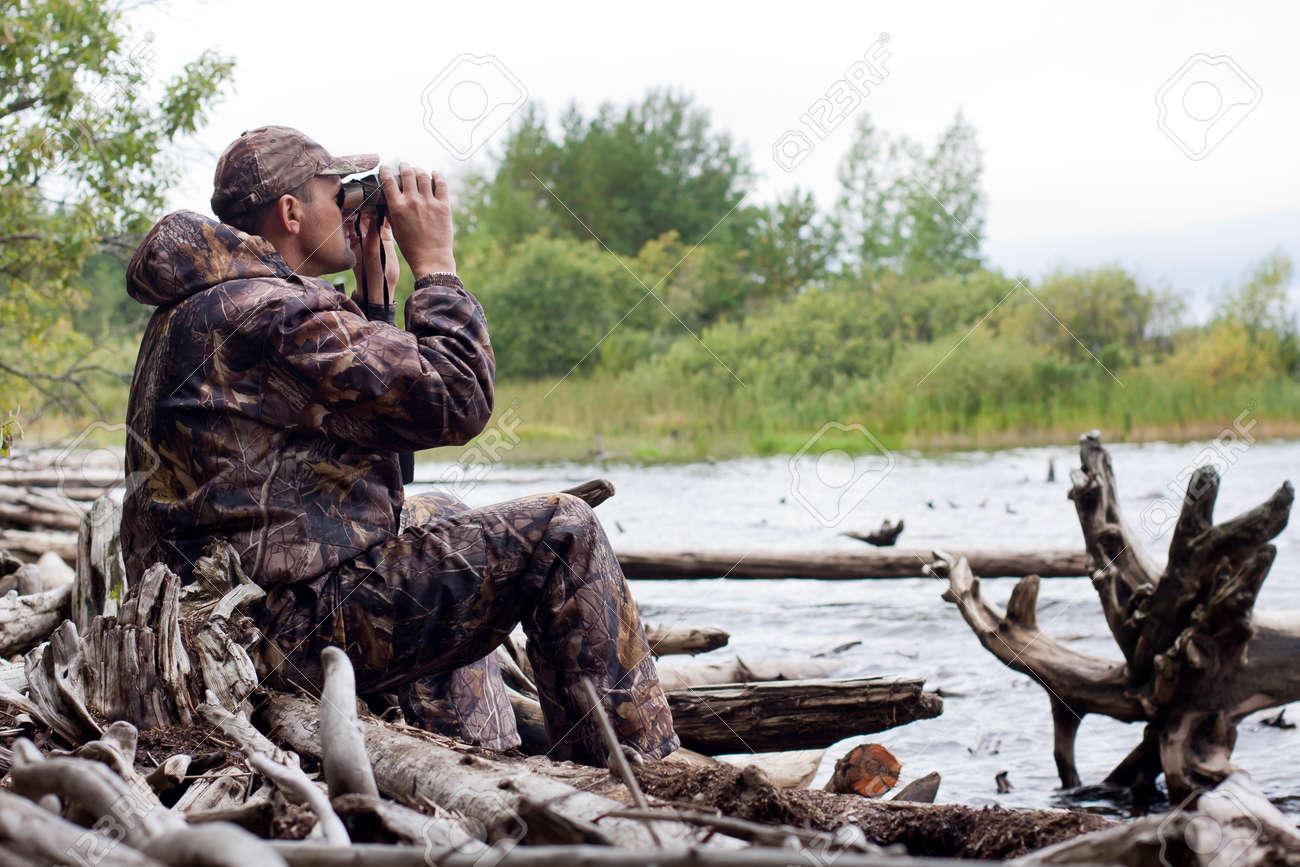 hunter looking through binoculars on the river - 34870408