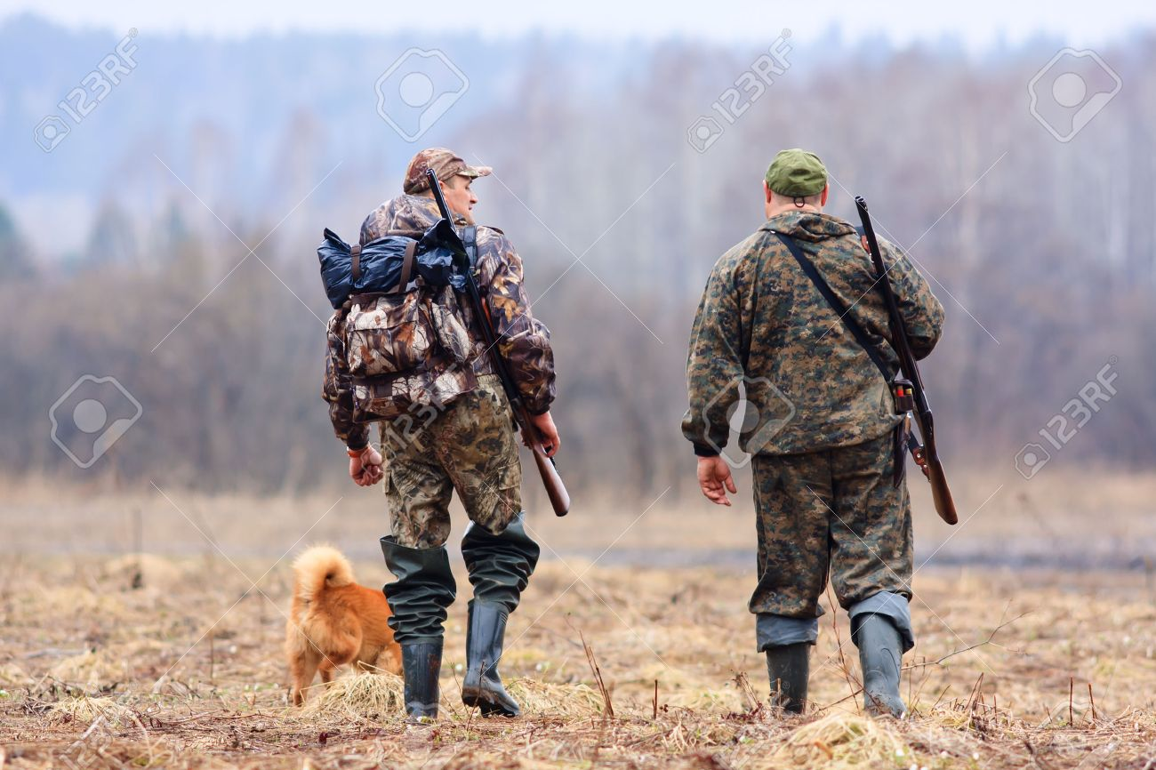 two hunters and dog on the field - 36988869