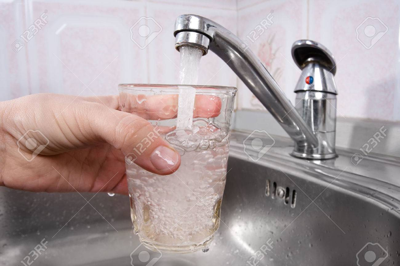 Hand Holding Glass Of Water Poured From Kitchen Faucet Stock Photo ...