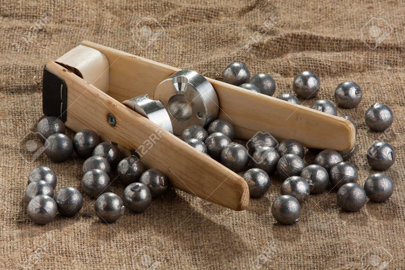 homemade bullet mold and ball-shaped bullets on burlap background