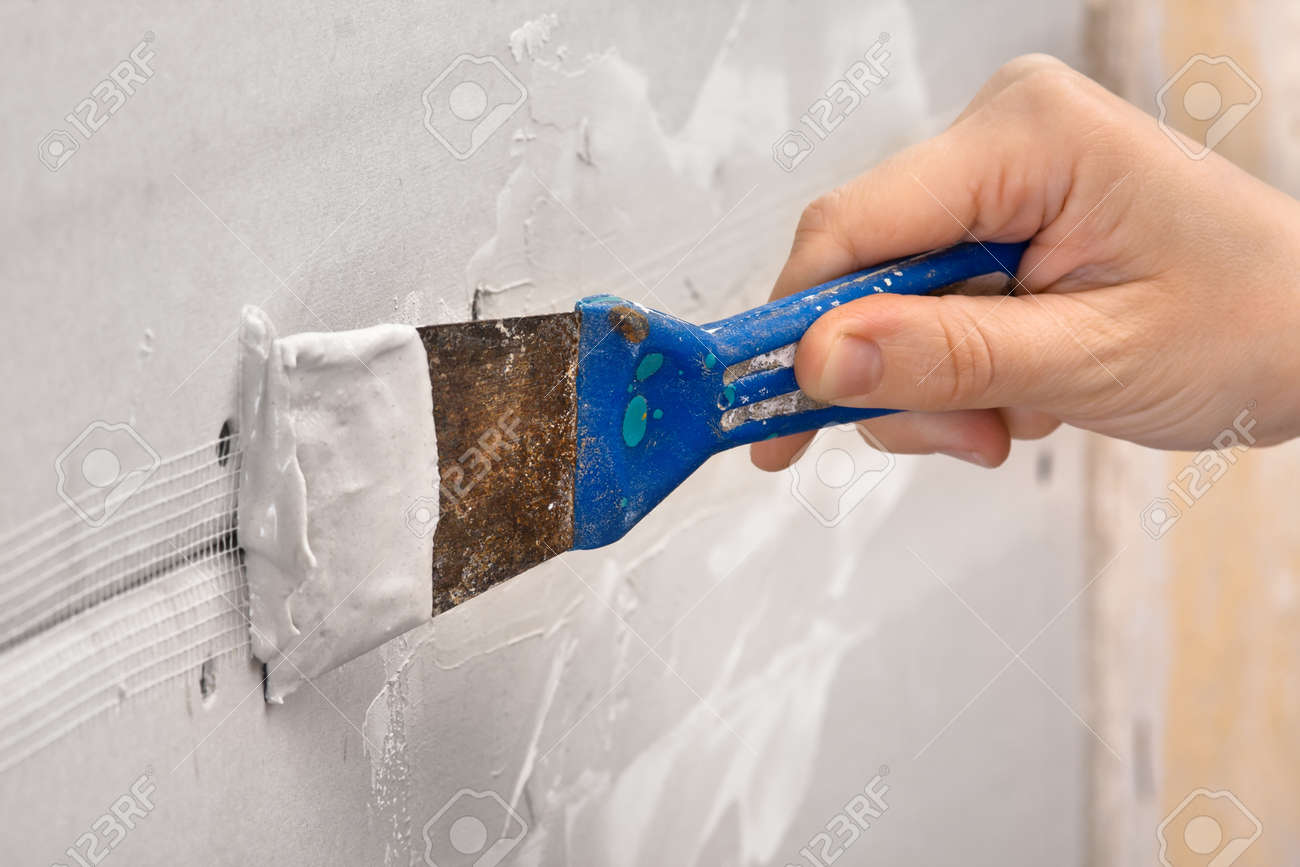 hand plastering a wall with spatula during repair - 56304700