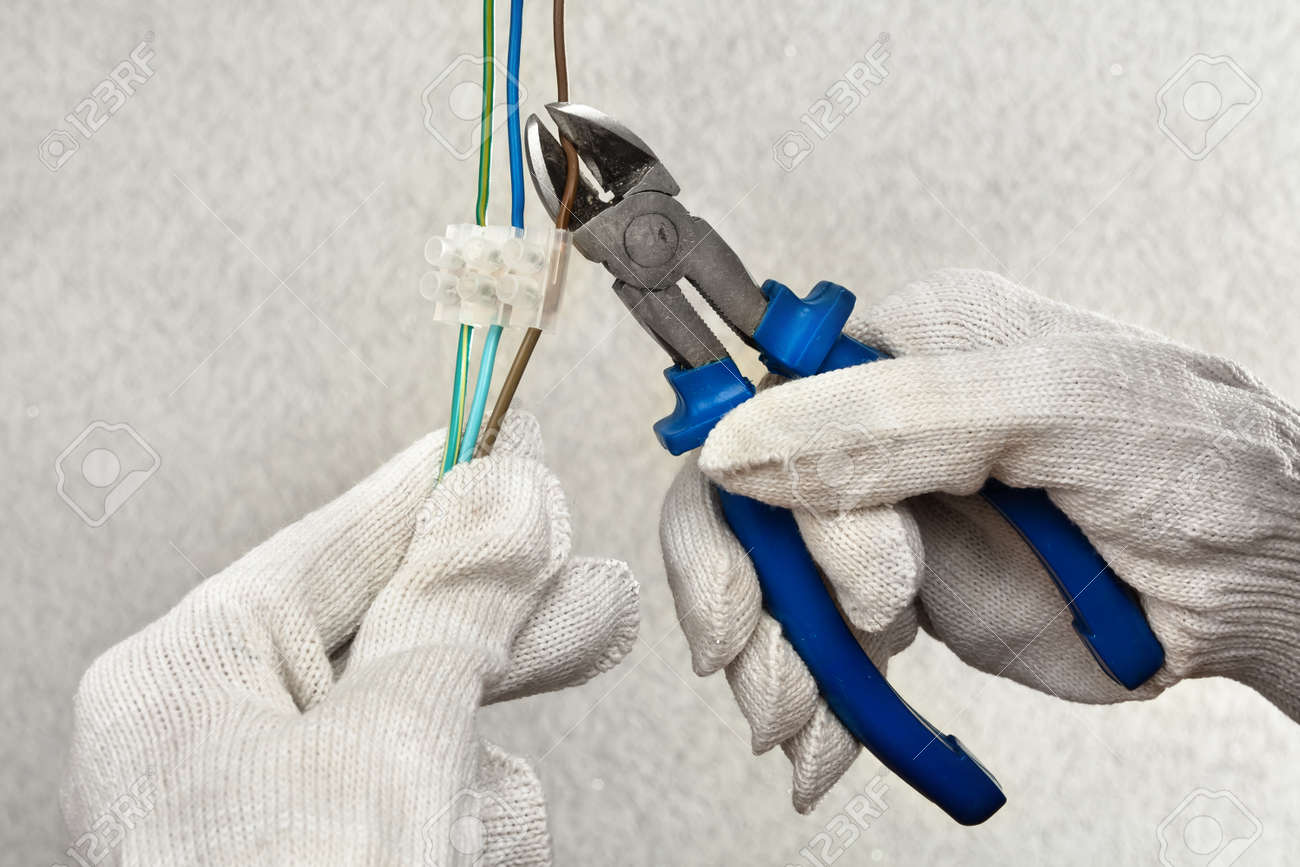 Hands Of Electrician In Gloves Cutting Wires With Clippers Stock ...
