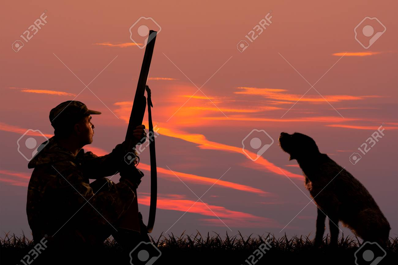 silhouettes of a hunter and a dog who are sitting at sunset background on the hunting - 122796415