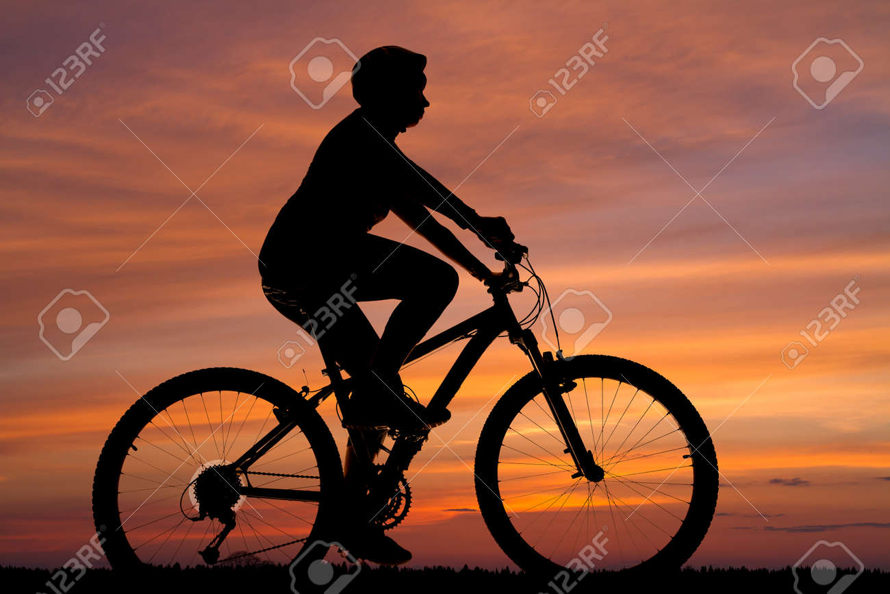 silhouette of a female cyclist riding against the sunset sky - 146796946