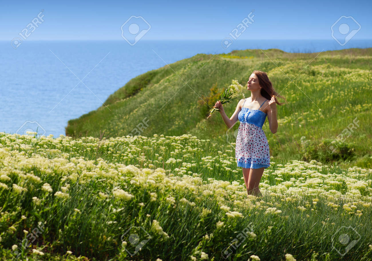 Young woman walking among the blooming yarrow at the seaside Stock Photo - 13805508