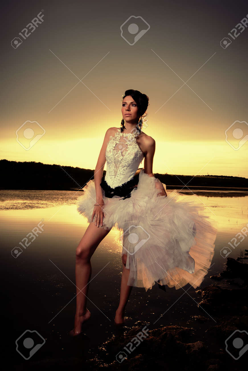 The modern bride standing at the riverside at golden sunset Standard-Bild - 14996135