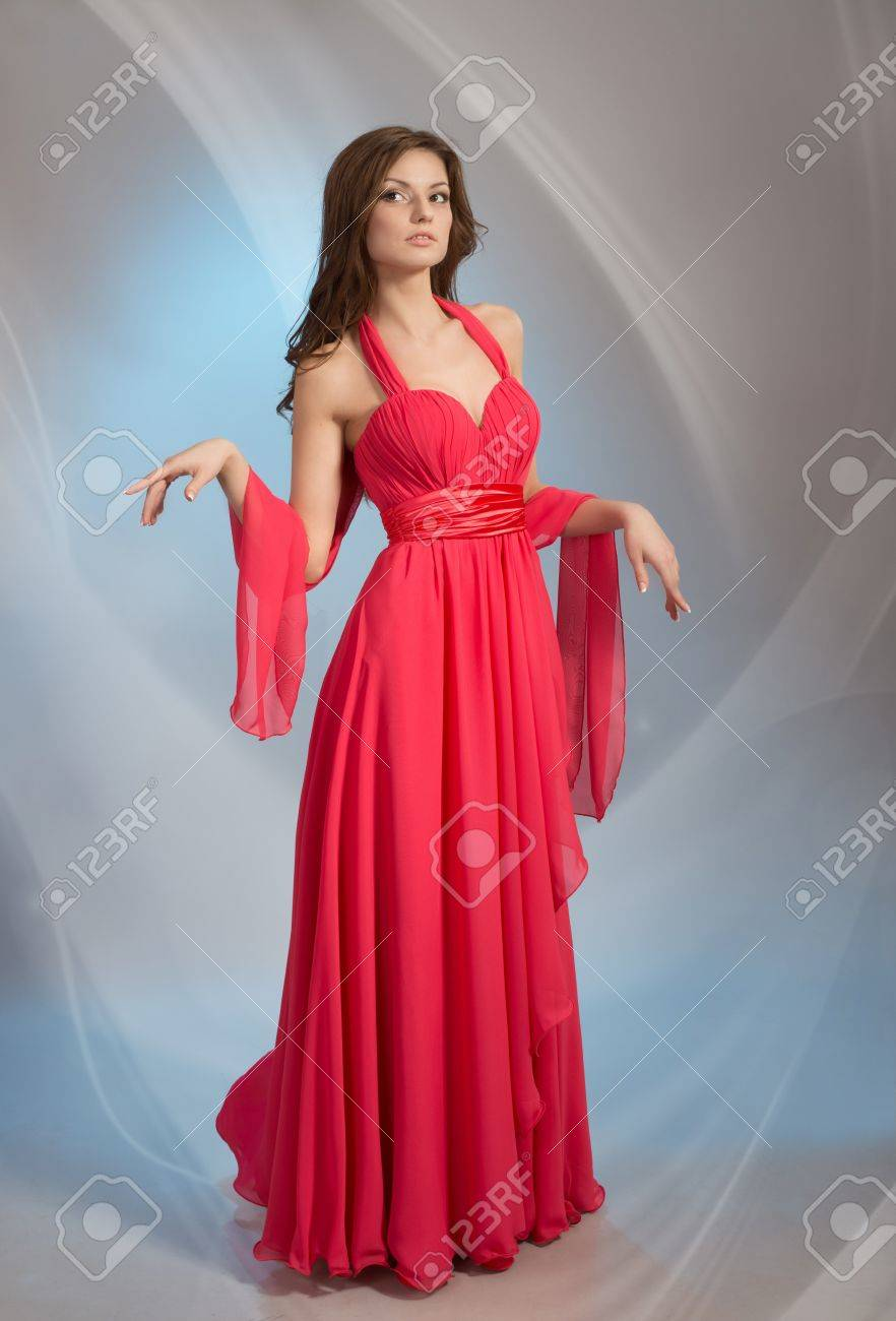 Beautiful young woman in red evening dress, on grey background Stock Photo - 17341289