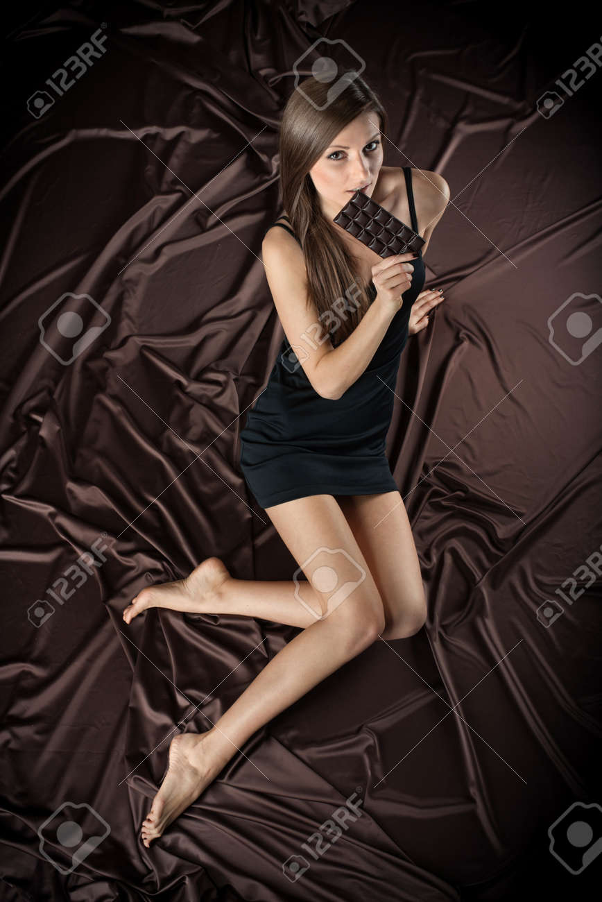 Pretty young woman nibbling the bar of chocolate, view from above, brown background Stock Photo - 17501576