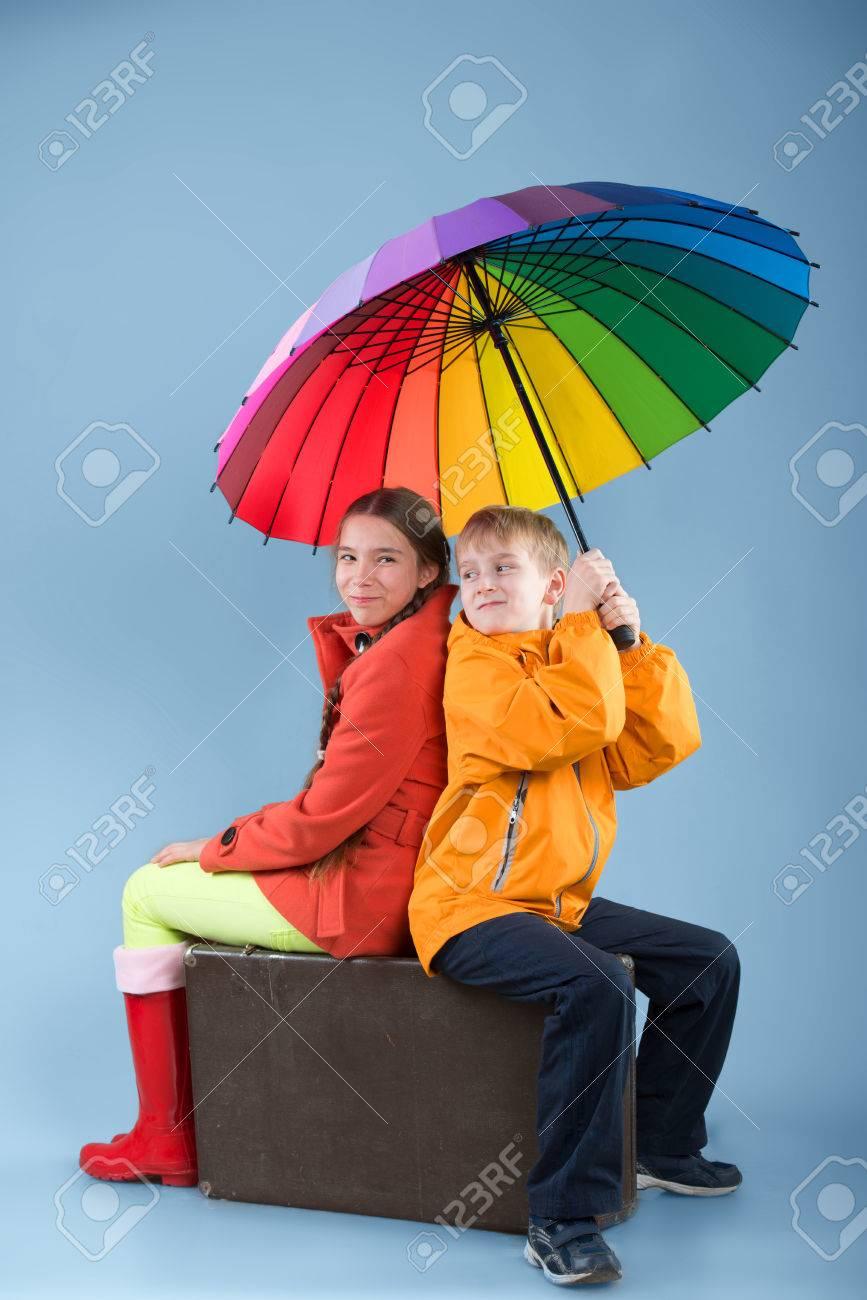 banque dimages fille et garon avec un parapluie color assis sur un vieux sac de voyage - Parapluie Color