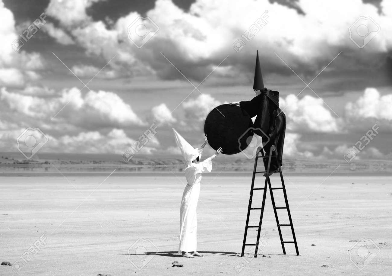 Figures étranges à manteau noir et un manteau blanc fixer la lune noire à  motifs firmament
