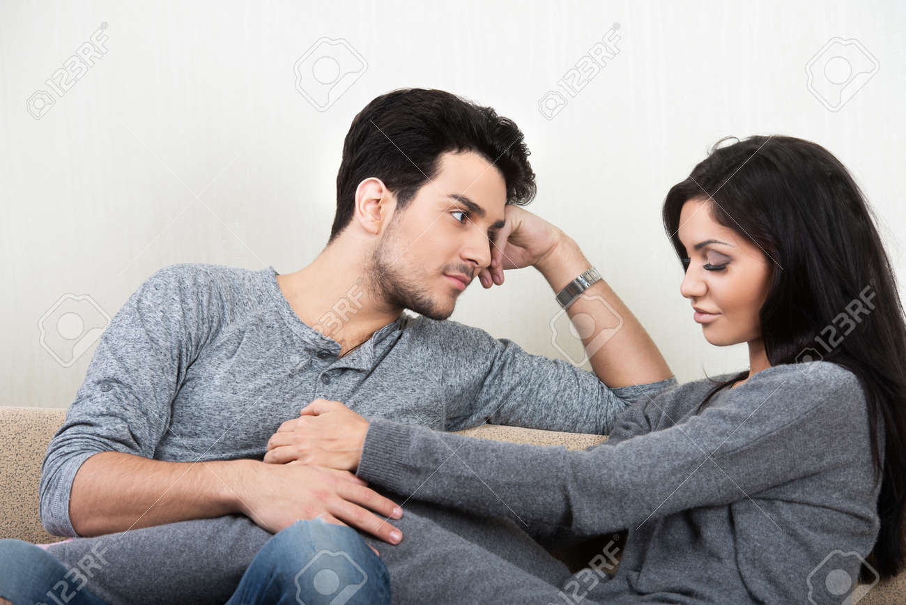 young happy couple talking each other sitting on a sofa stock photo