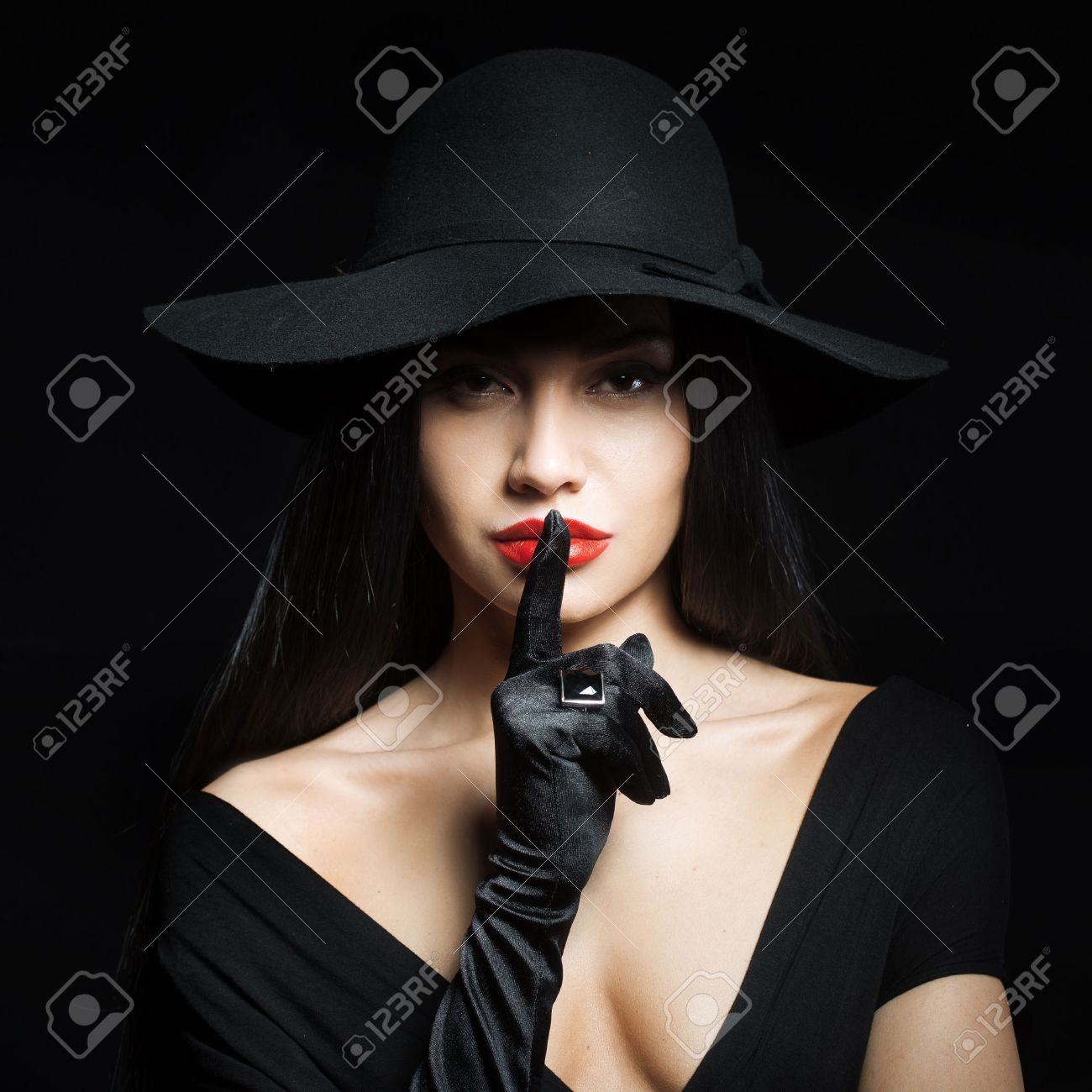 Woman in big black hat making a silence gesture, studio portrait,