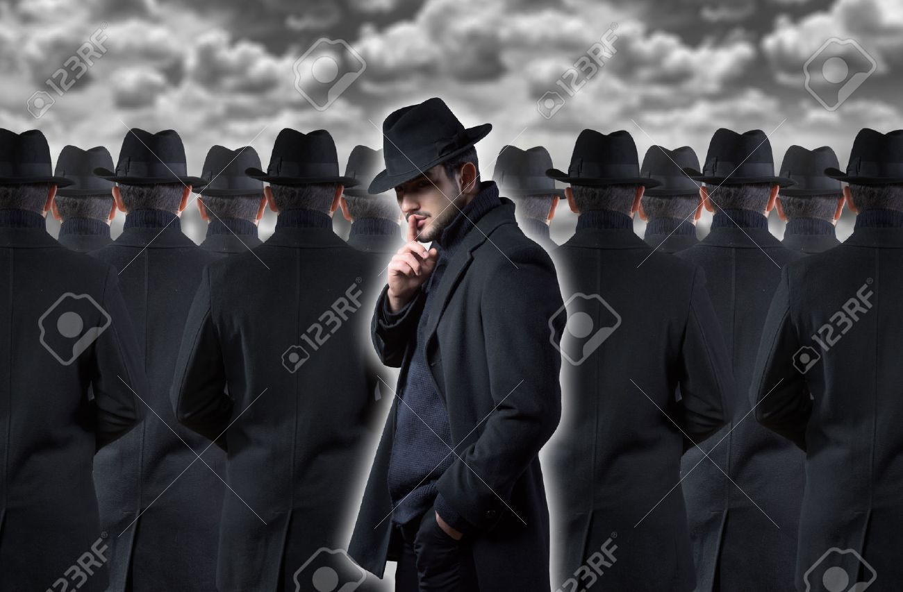 Mysterious man making a silence gesture while standing out from the crowd - 50132944