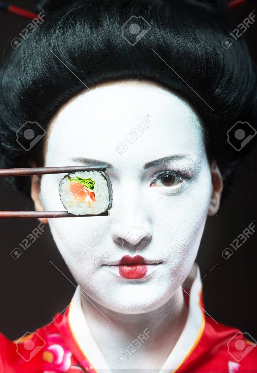Portrait of a woman in geisha makeup eating sushi Stock Photo - 79331384