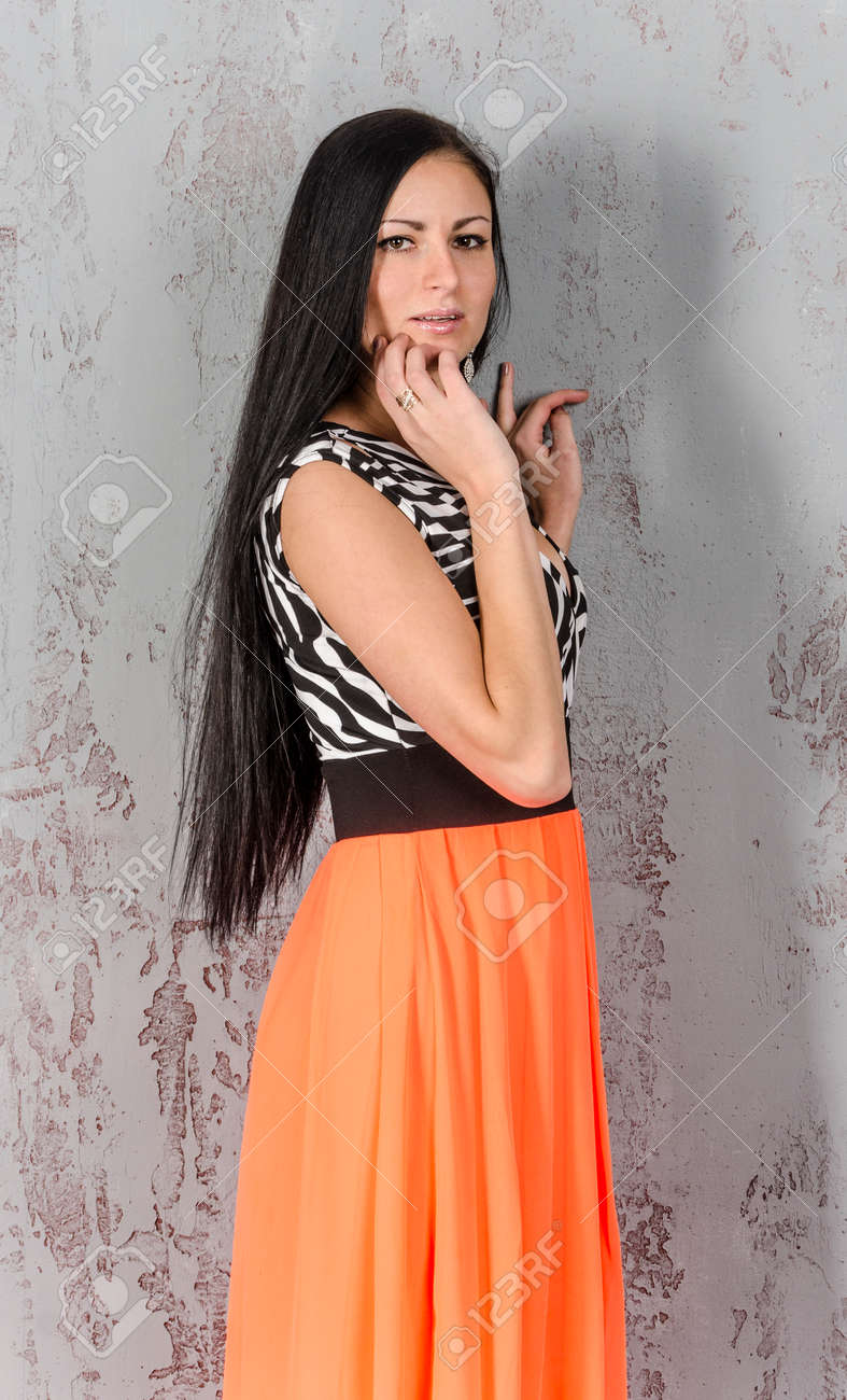 fba4d1448c1 Beautiful slim brunette girl in a bright dress and summer long skirt Stock  Photo - 71853900