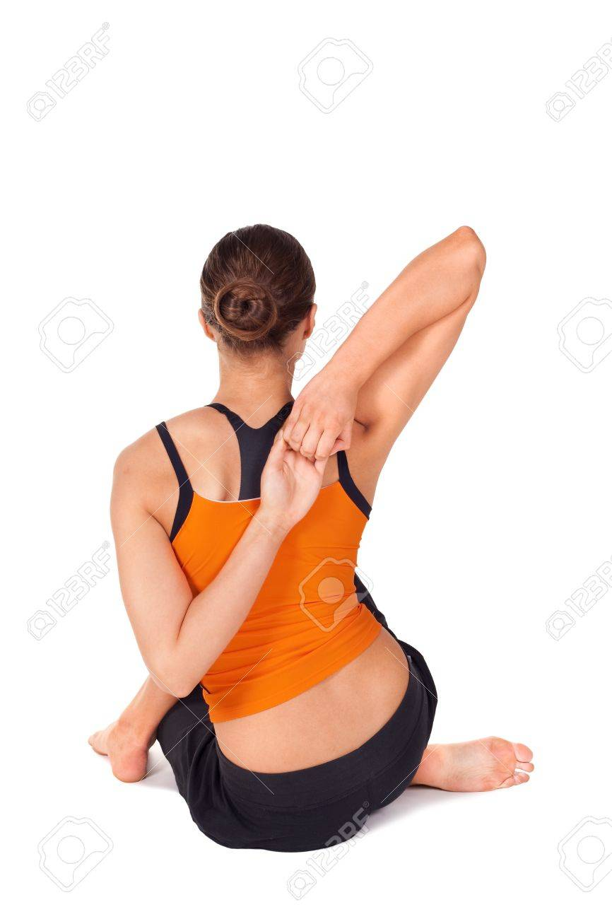 Woman doing yoga exercise called Cow Face Pose, sanskrit name:..