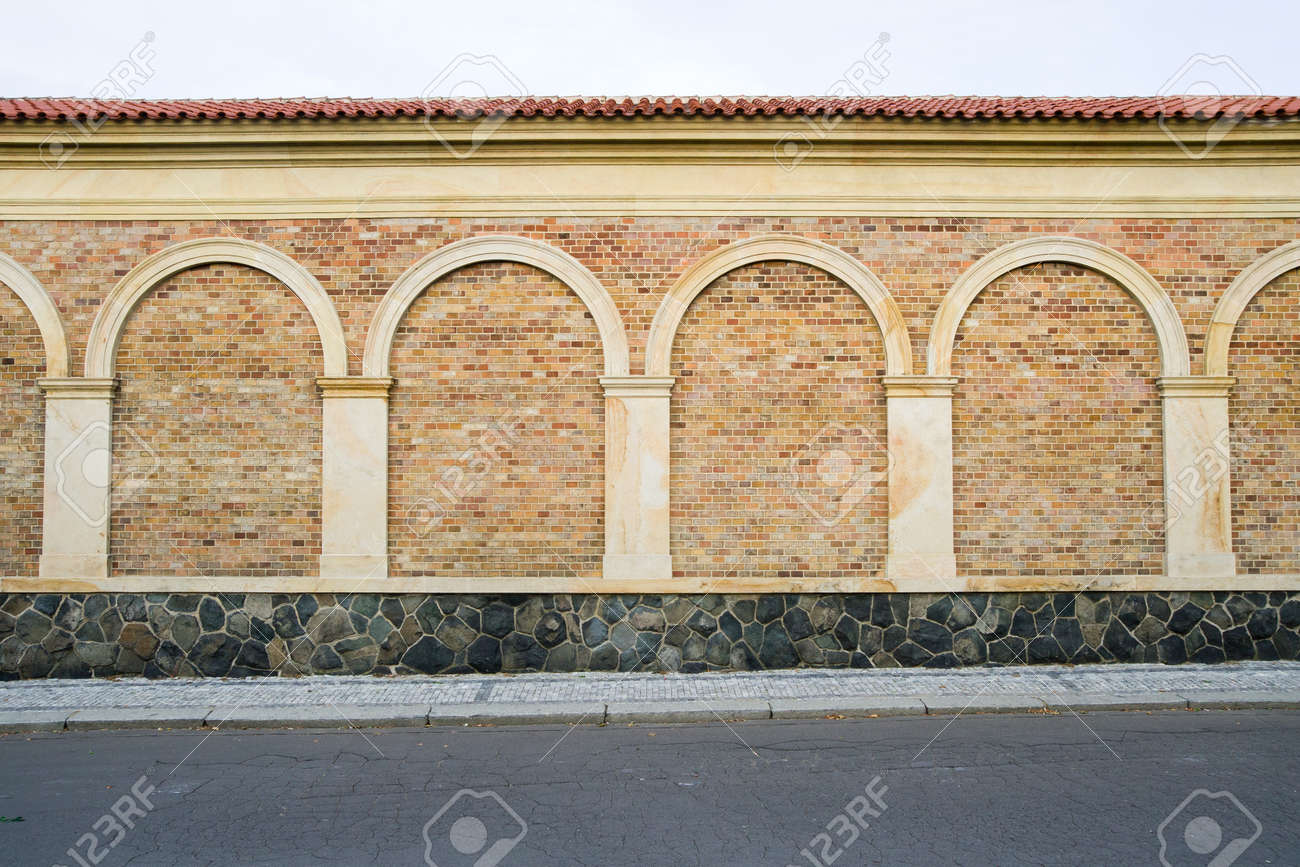 Elegant Classic Decorative Brick Wall With Columns Arches And Stone Base  Next To The Sidewalk And With Decorative Brick Walls.