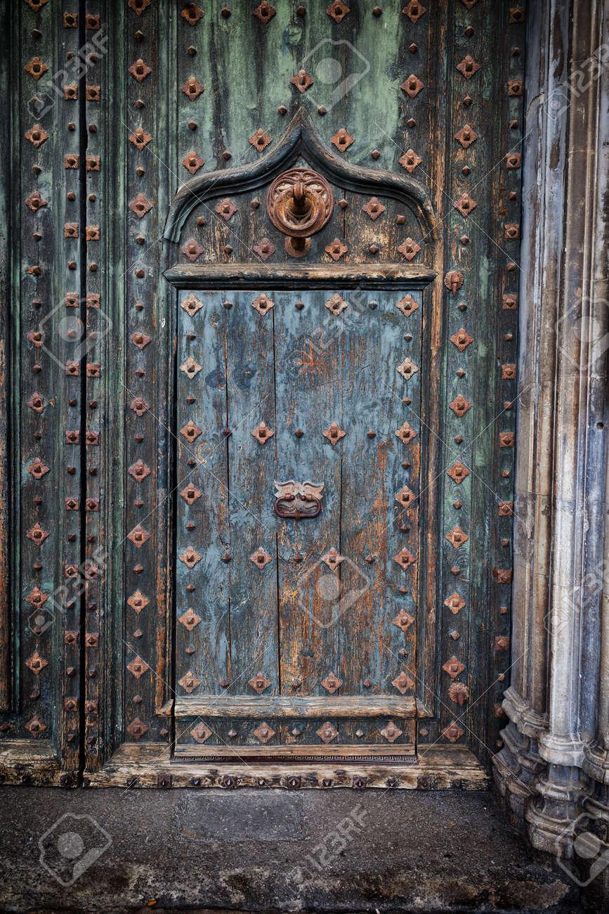 Old door within door to the Girona Cathedral in Spain aged wood with metal reinforcement & Reinforced Door Stock Photos. Royalty Free Reinforced Door Images