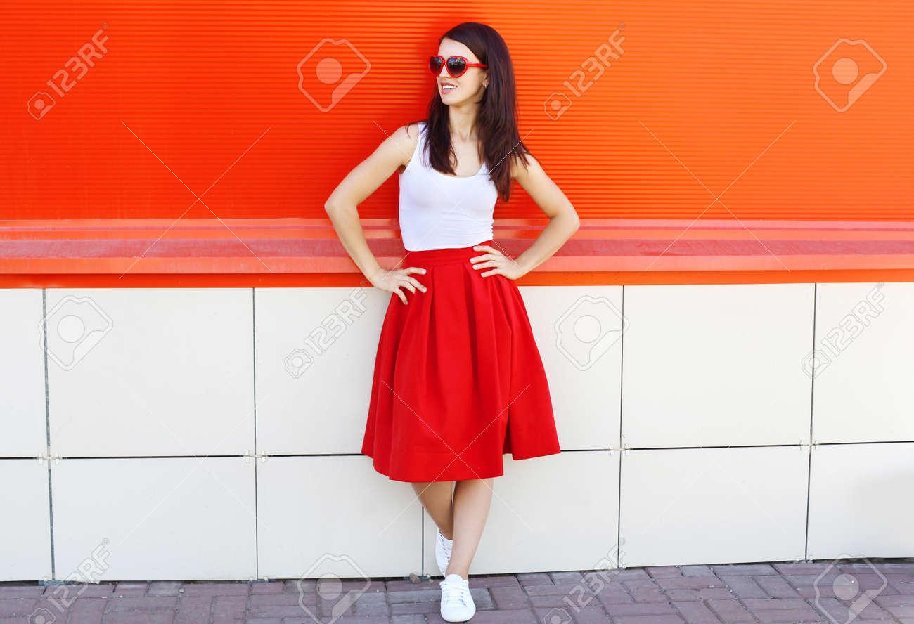 l'atteggiamento migliore 9a8c4 58c3a Bella donna bruna che indossa occhiali da sole e gonna rossa in vista del  profilo della città