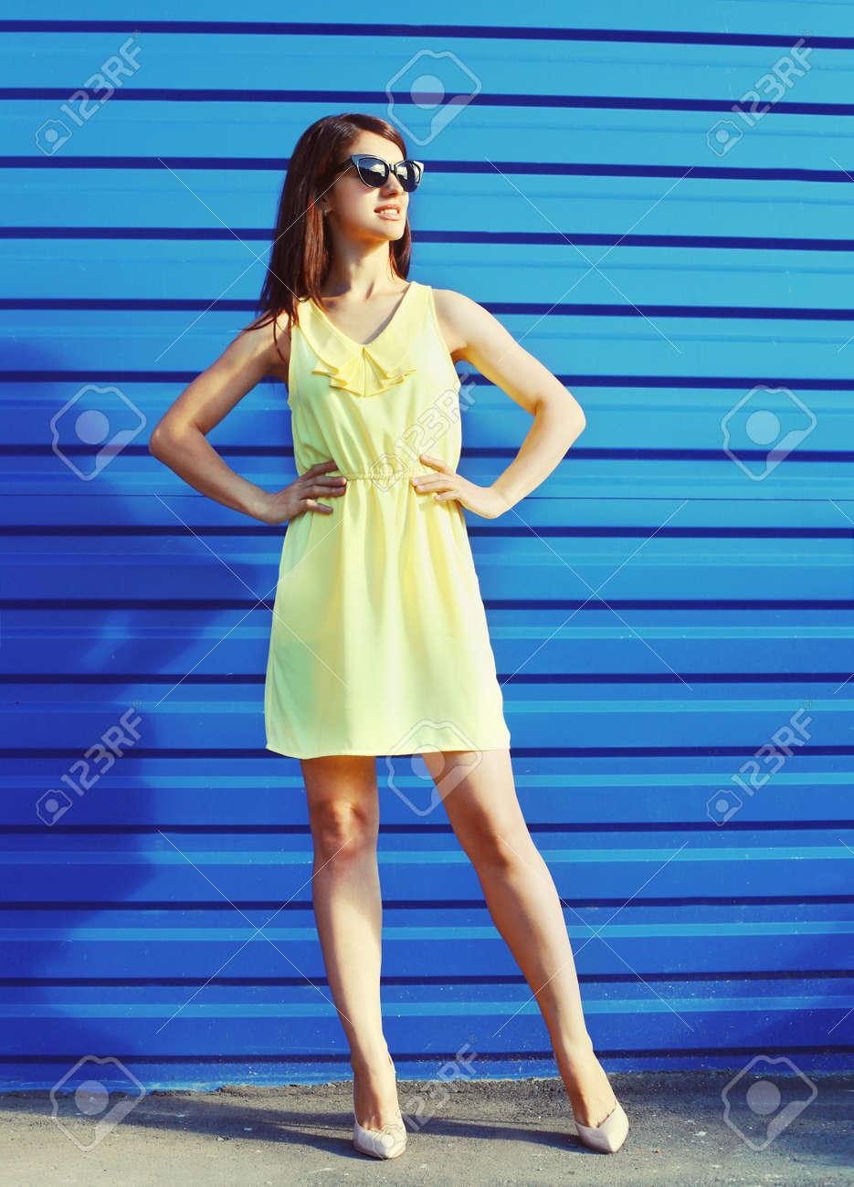 schöne junge frau, die eine sonnenbrille und ein gelbes kleid über blauem  hintergrund trägt