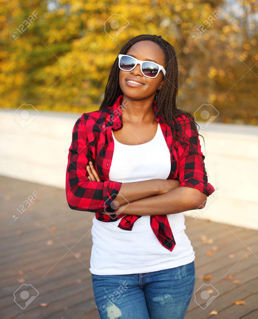 014fc96d2450 Banque d images - Portrait belle femme africaine souriant vêtu d un  lunettes de soleil, chemise à carreaux rouge journée d automne ensoleillée